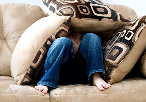 enfant-peur-angoisse-cachette-canapé-coussin-jean